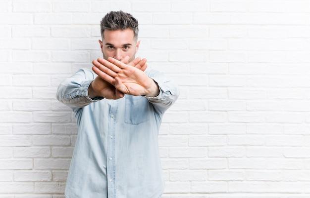 Giovane uomo bello contro un muro di mattoni che fa un gesto di diniego Foto Premium