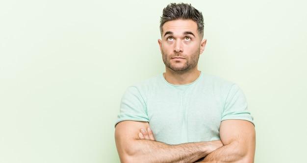 Giovane uomo bello contro un muro verde stanco di un compito ripetitivo. Foto Premium