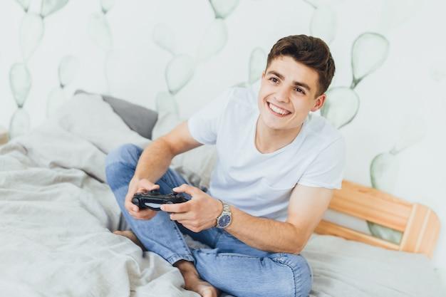 Il giovane bell'uomo sul letto nella sua stanza gioca con un joystick. Foto Premium