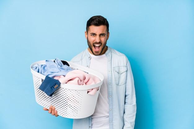 Giovane uomo bello che fa lavanderia isolato urlando molto arrabbiato e aggressivo. Foto Premium