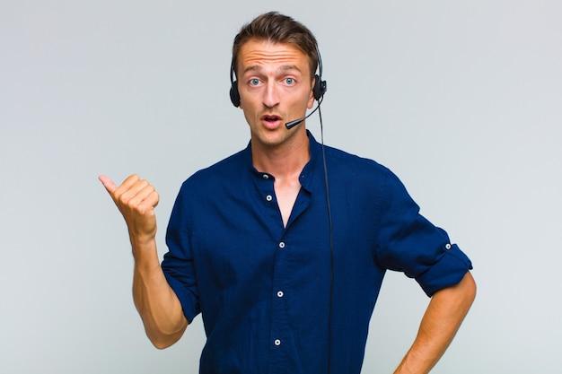 Giovane uomo bello che guarda stupito incredulo, indicando un oggetto sul lato e dicendo wow, incredibile Foto Premium