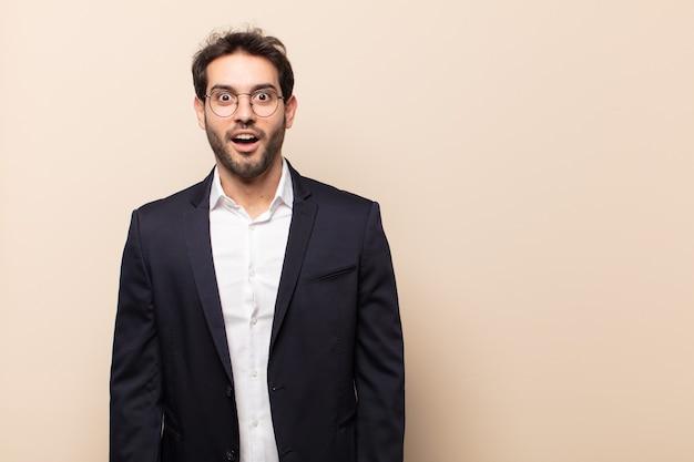Giovane uomo bello che sembra molto scioccato o sorpreso, fissando con la bocca aperta dicendo wow Foto Premium