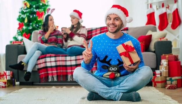 Babbo Natale Uomo Bello.Giovane Uomo Bello In Un Cappello Da Babbo Natale Con Un Regalo Di Natale Foto Premium