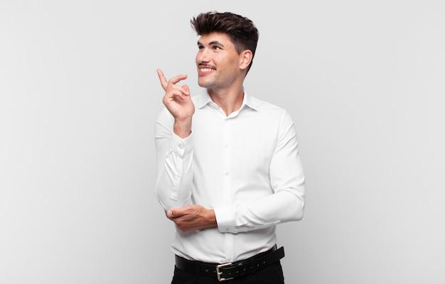 Giovane uomo bello sorridente felicemente e guardando di traverso, chiedendosi, pensando o avendo un'idea Foto Premium