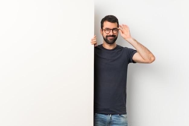 Giovane uomo bello con la barba che tiene un grande cartello vuoto con gli occhiali e felice Foto Premium