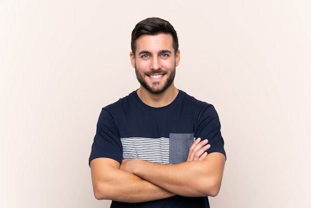 Giovane uomo bello con la barba sopra isolato mantenendo le braccia incrociate in posizione frontale Foto Premium