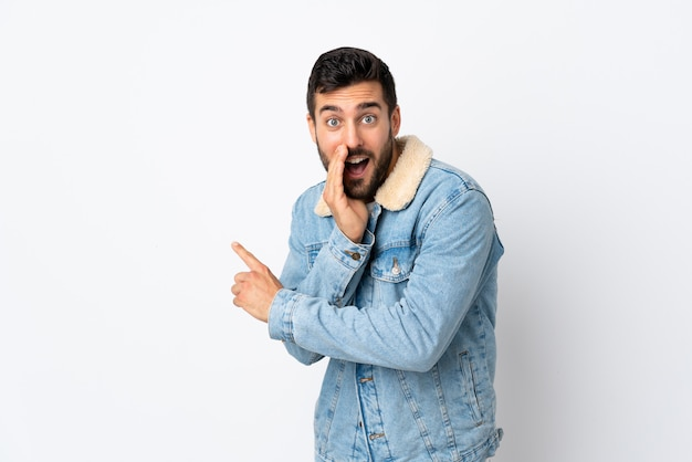 Giovane uomo bello con la barba isolato sul muro bianco che punta verso il lato per presentare un prodotto e sussurrando qualcosa Foto Premium