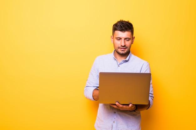 Giovane uomo bello con il portatile su sfondo giallo Foto Premium