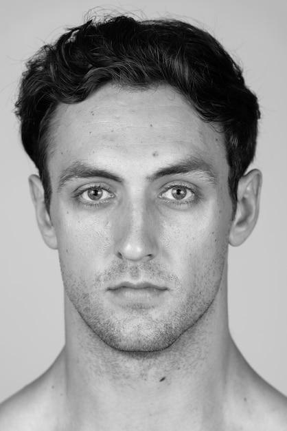 Giovane uomo muscoloso bello con capelli ondulati a torso nudo isolato in bianco e nero Foto Premium