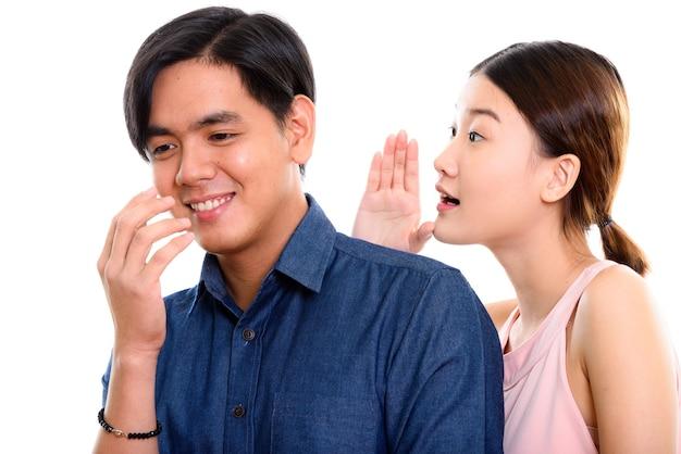 Giovane coppia asiatica felice sorridente con la donna che bisbiglia all'uomo Foto Premium