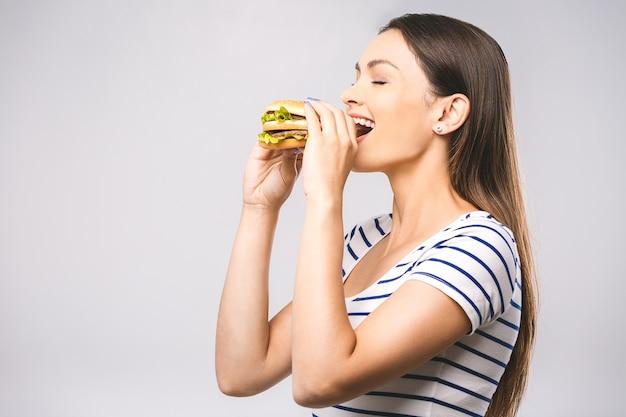 Giovane bella donna felice che mangia hamburger Foto Premium