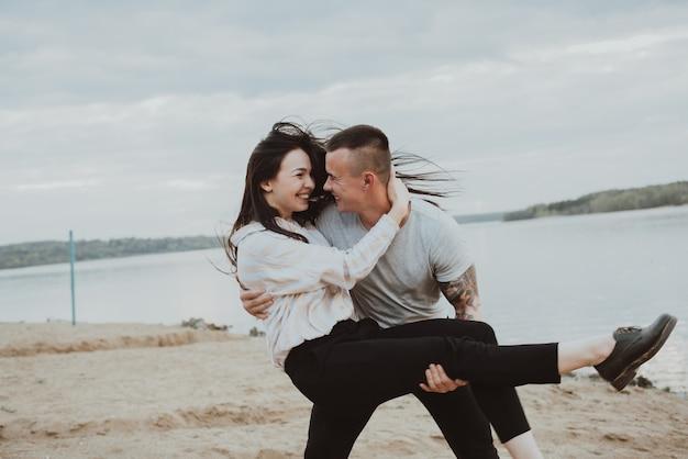 Giovani coppie felici che hanno divertimento sulla sabbia sulla spiaggia in estate. la foto è sfocata a causa del movimento e della velocità dell'otturatore ridotta Foto Premium
