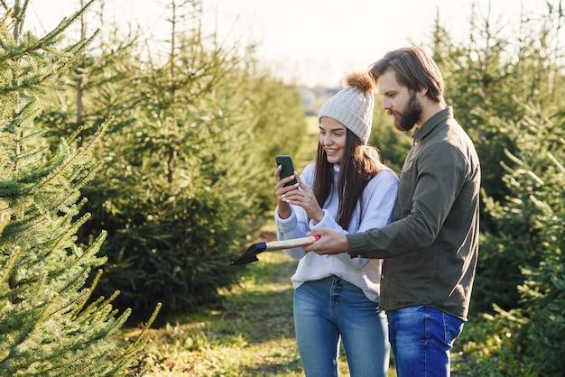 Giovane famiglia felice che sceglie l'albero di natale alla piantagione che prepara le vacanze invernali. Foto Premium