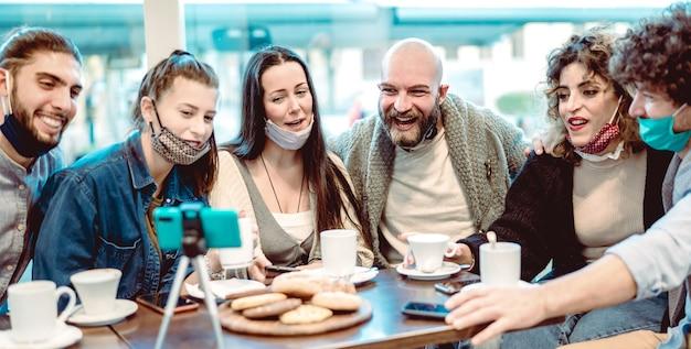Giovani amici felici che condividono contenuti sulla piattaforma di streaming indossando una maschera per il viso Foto Premium