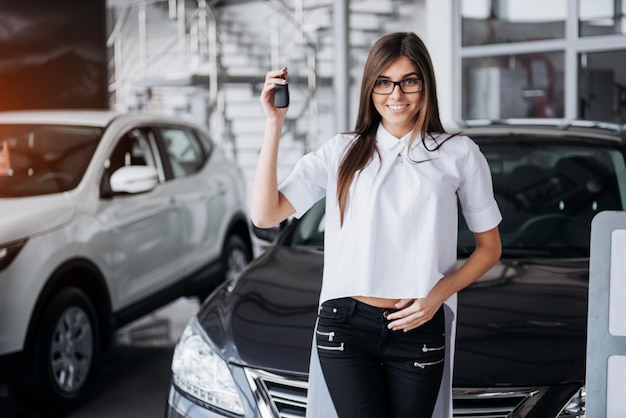 Giovane donna felice vicino all'automobile con le chiavi in mano Foto Premium