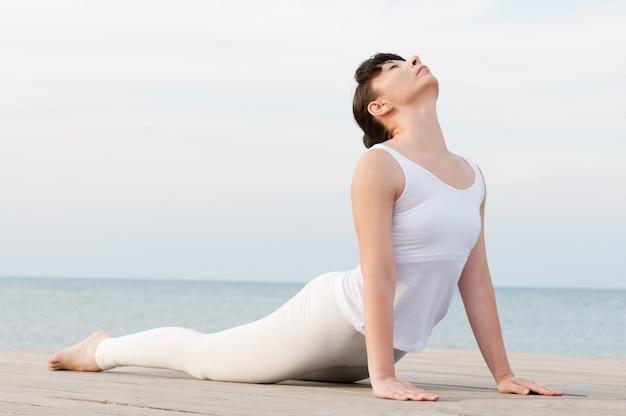 Giovane donna in buona salute che fa posizione di yoga in mare: posa della cobra Foto Premium