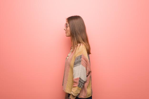 Giovane donna hippie su sfondo rosa sul lato che guarda in avanti Foto Premium