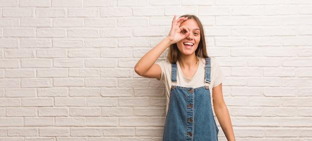 Donna giovane hipster fiduciosa facendo gesto ok sull'occhio Foto Premium
