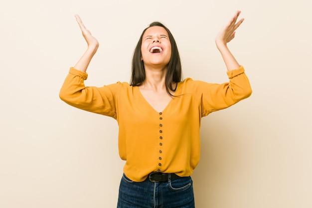 Giovane donna ispanica contro una parete beige che grida al cielo, alzando lo sguardo, frustrata. Foto Premium