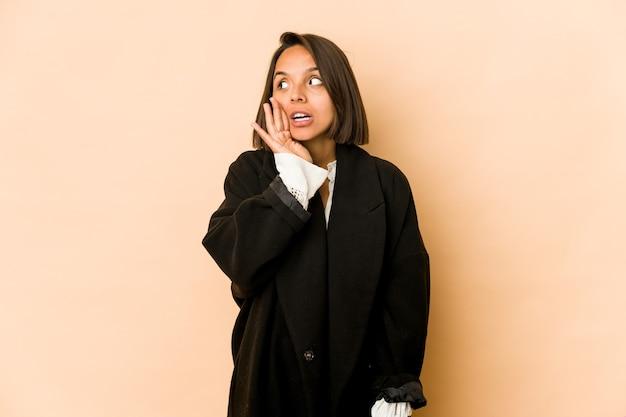 La giovane donna ispanica isolata sta dicendo una notizia segreta di frenata calda e sta guardando da parte Foto Premium