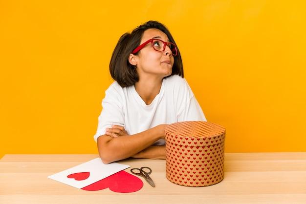 Giovane donna ispanica che prepara un regalo di san valentino isolato sognando di raggiungere obiettivi e scopi Foto Premium