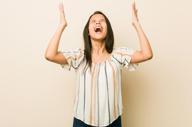 Giovane donna ispanica che grida al cielo, alzando lo sguardo, frustrata. Foto Premium