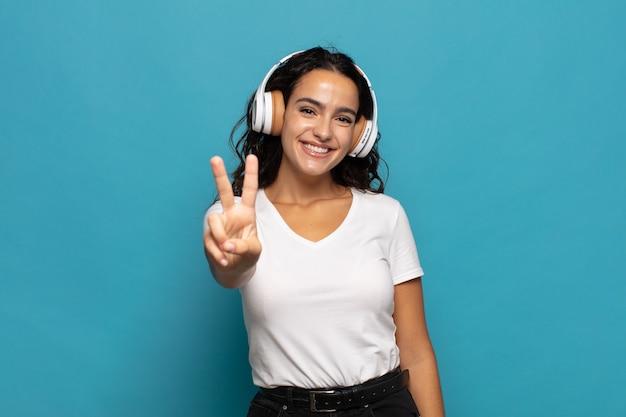 Giovane donna ispanica sorridente e dall'aspetto amichevole, mostrando il numero due o il secondo con la mano in avanti, il conto alla rovescia Foto Premium