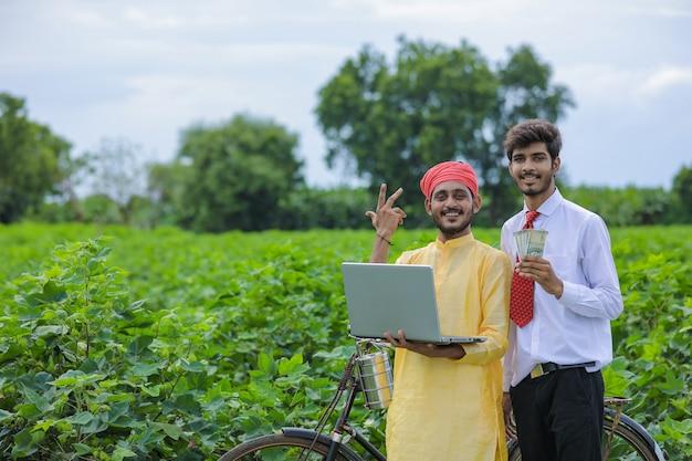Giovane agronomo indiano che mostra alcune informazioni all'agricoltore nel computer portatile al campo di cotone Foto Premium