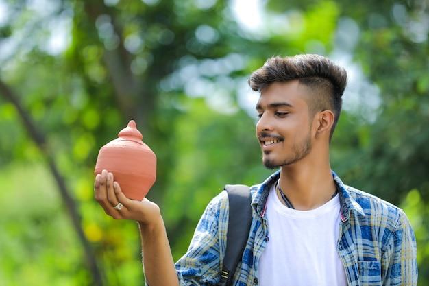 Giovani indiani college boy holding argilla salvadanaio in mano su sfondo natura Foto Premium