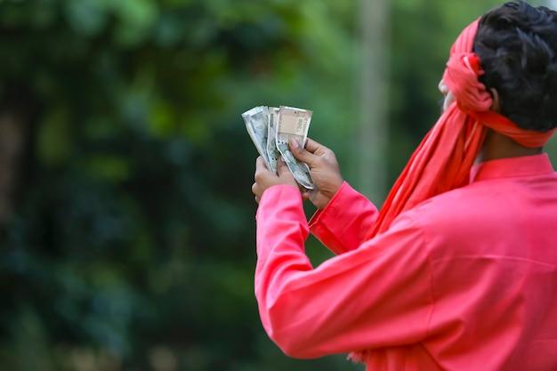 Giovane agricoltore indiano che conta soldi Foto Premium