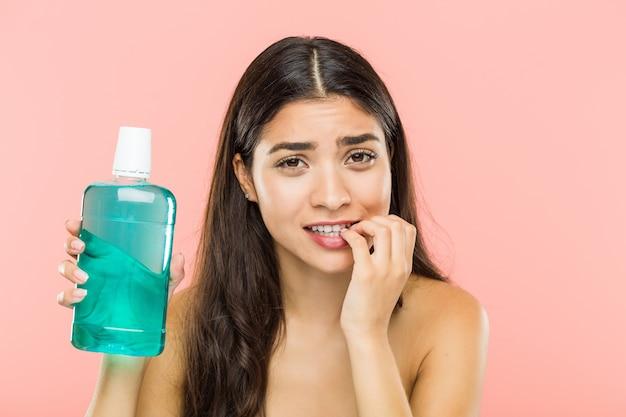 Giovane donna indiana che tiene una bottiglia di collutorio che morde le unghie, nervosa e molto ansiosa. Foto Premium