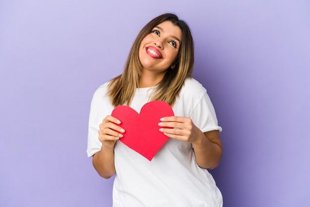 Giovane donna indiana che tiene un cuore di san valentino isolato sognando di raggiungere obiettivi e scopi Foto Premium