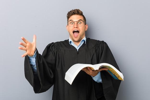 Giovane giurista che tiene un libro che celebra una vittoria o un successo Foto Premium