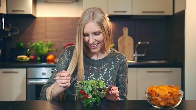 Giovane signora che preferisce l'insalata alle patatine fritte. Foto Premium