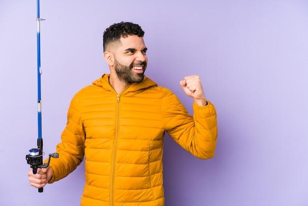 Giovane pescatore latino in possesso di una canna isolata giovane pescatore latino con in mano un giovane uomo latino che gioca a canestro isolato pugno alzato dopo una vittoria, concetto vincitore. <mixto> Foto Premium