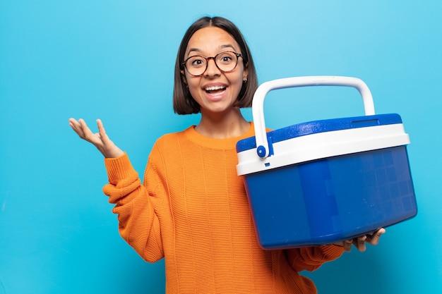 Giovane donna latina che si sente felice, sorpresa e allegra, sorridente con atteggiamento positivo, realizzando una soluzione o un'idea Foto Premium