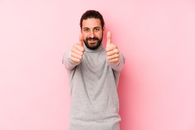 Uomo giovane capelli lunghi isolato su uno sfondo rosa con il pollice in alto, applausi per qualcosa, supporto e concetto di rispetto. Foto Premium
