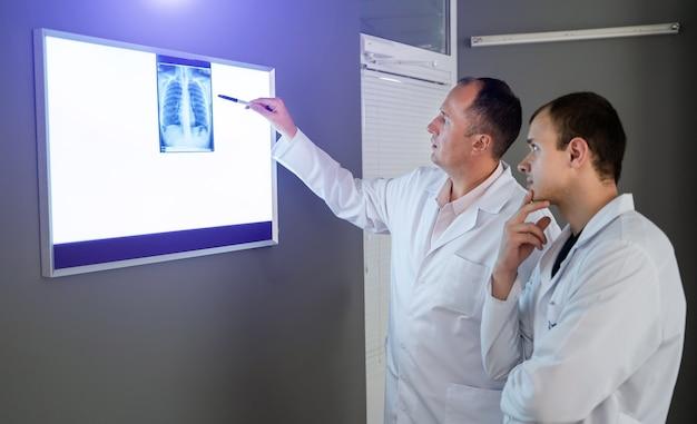 Giovani medici maschi che esaminano attentamente i raggi x e discutono la diagnosi. Foto Premium