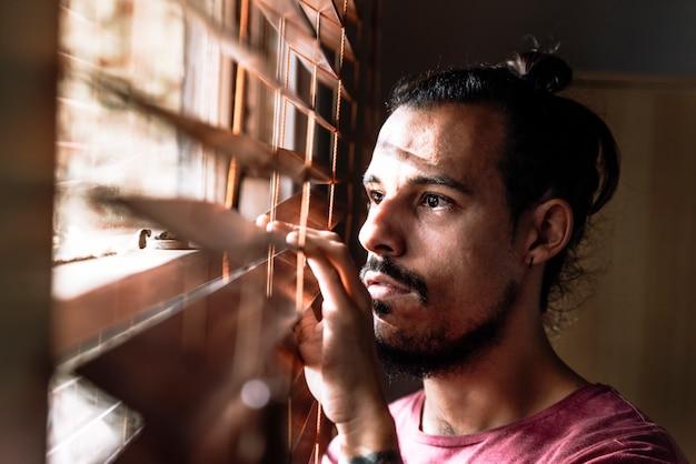 Un giovane maschio che guarda attraverso i ciechi della finestra per stare al sicuro durante l'epidemia di coronavirus Foto Premium