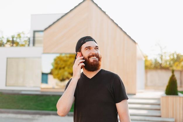 Giovane maschio sorridente e parlando al suo telefono e guardando lontano davanti alla sua nuova casa Foto Premium