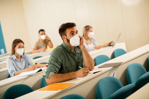 Giovane studente maschio che indossa la maschera medica protettiva per il viso per la protezione da virus in aula Foto Premium