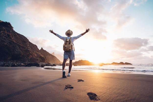 Il giovane arma steso dal mare all'alba che gode della libertà e della vita, concetto di benessere di viaggio della gente Foto Premium