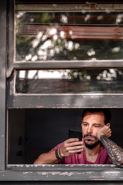 Un giovane annoiato durante il blocco di covid 19 a causa di un sovradosaggio di smartphone. Foto Premium