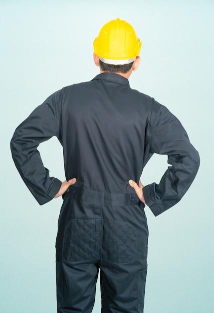 Giovane uomo in tuta casco elmetto protettivo isolato su sfondo blu Foto Premium