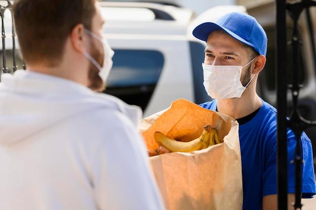 Giovane uomo che consegna generi alimentari con maschera Foto Premium