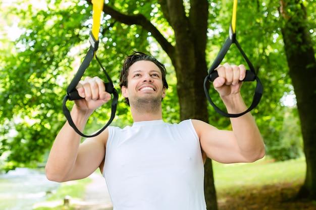 Giovane che si esercita con l'imbracatura dell'istruttore della sospensione nel parco della città sotto gli alberi di estate per il fitness sportivo Foto Premium