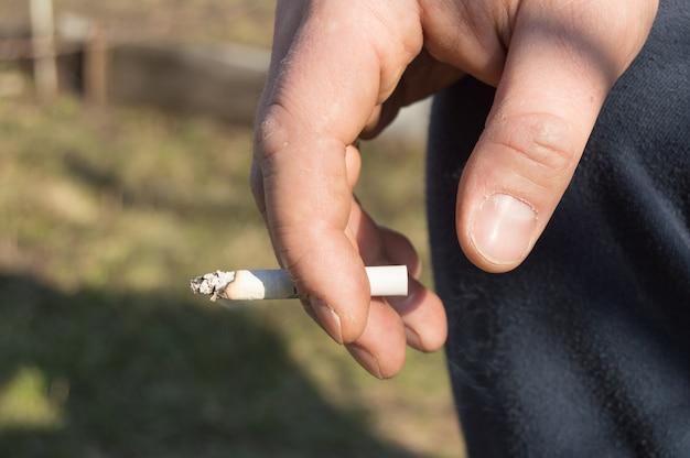 Un giovane uomo che tiene una sigaretta in mano, seduti all'aperto Foto Premium