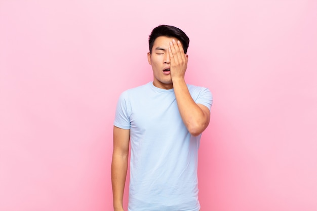 Giovane che sembra assonnato, annoiato e sbadigliante, con un mal di testa e una mano che copre metà del viso sul muro Foto Premium