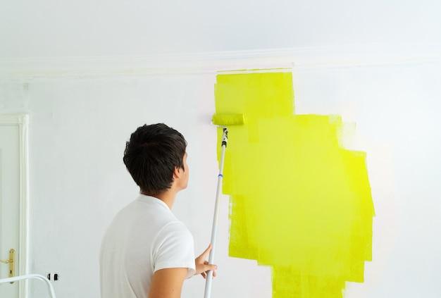 Giovane uomo pittura parete illuminante di colore giallo nella stanza intonacata bianca Foto Premium
