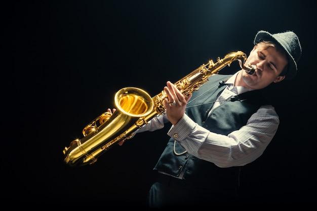 Giovane uomo che suona il sassofono Foto Premium